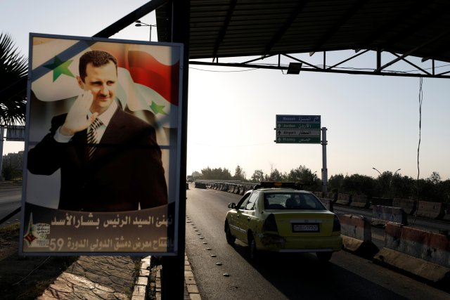 A poster of Syrian President Bashar al-Assad is seen on the main road to the airport in Damascus, Syria April 14, 2018. REUTERS/Omar Sanadiki