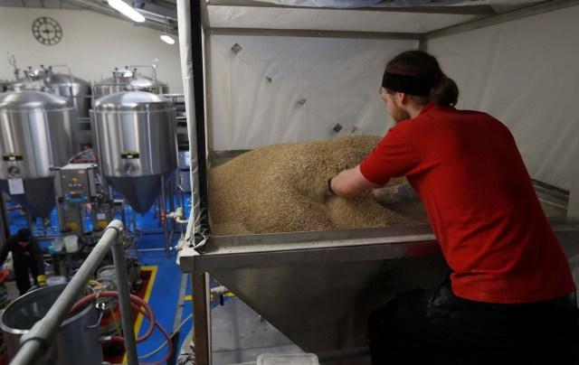 Un trabajador prepara malta de cebada al comienzo del proceso de fabricación de la pale ale de Harry y Meghan en la cervecería Windsor and Eton en Windsor, Gran Bretaña, el 11 de abril de 2018. Fotografía tomada el 11 de abril de 2018. REUTERS / Peter Nicholls