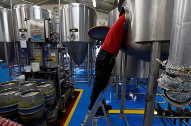 Un trabajador limpia un puré en la cervecería Windsor and Eton en Windsor, Gran Bretaña, el 11 de abril de 2018. Fotografía tomada el 11 de abril de 2018. REUTERS / Peter Nicholls