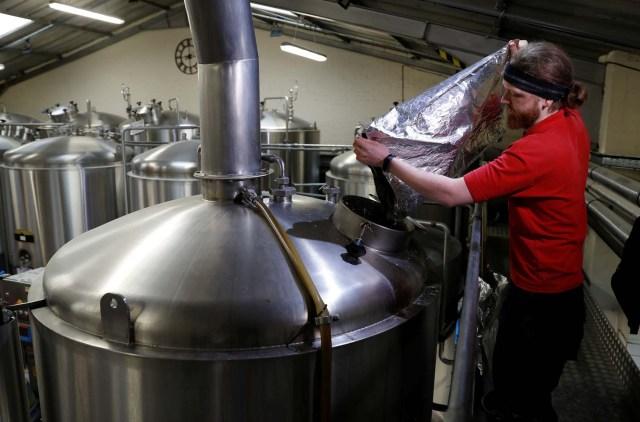 Un trabajador vierte saltos del estado de Washington de los EE. UU. En un macerado en la cervecería Windsor and Eton en Windsor, Gran Bretaña, el 11 de abril de 2018. Fotografía tomada el 11 de abril de 2018. REUTERS / Peter Nicholls