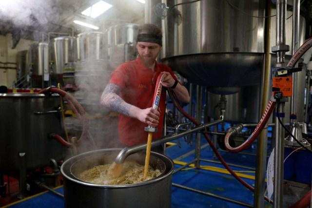 Un trabajador drena el líquido de un puré en la cervecería Windsor and Eton en Windsor, Gran Bretaña, el 11 de abril de 2018. Fotografía tomada el 11 de abril de 2018. REUTERS / Peter Nicholls