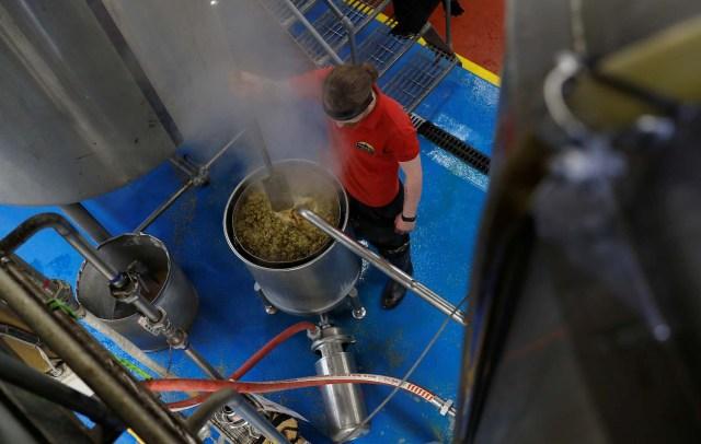 Un trabajador extrae líquido de una maceración y salta en la cervecería Windsor and Eton en Windsor, Gran Bretaña, el 11 de abril de 2018. Fotografía tomada el 11 de abril de 2018. REUTERS / Peter Nicholls