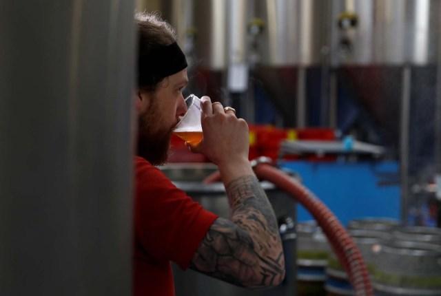 Un trabajador prueba el líquido de un puré en la cervecería Windsor and Eton en Windsor, Gran Bretaña, el 11 de abril de 2018. Fotografía tomada el 11 de abril de 2018. REUTERS / Peter Nicholls