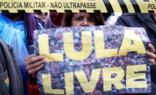 """Un partidario del ex presidente brasileño Luiz Inácio Lula da Silva protesta frente a la sede de la Policía Federal, donde Lula está encarcelado, en Curitiba, Brasil, el 17 de abril de 2018. El letrero dice: """"Lula gratis"""". REUTERS / Rodolfo Buhrer"""