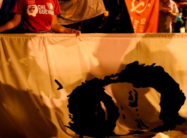 Un partidario del ex presidente brasileño Luiz Inácio Lula da Silva sostiene una bandera con la cara de Lula en un campamento cerca de la sede de la Policía Federal, donde Lula está preso, en Curitiba, Brasil, el 13 de abril de 2018. Fotografía tomada el 13 de abril de 2018. REUTERS / Rodolfo Buhrer