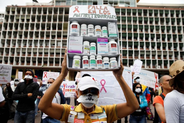 """A woman carrying empty medication containers takes part in a protest due to the shortages of medicines outside the Health Ministry in Caracas, Venezuela April 18, 2018. The placard reads, """"Shortage in antiretroviral medications"""". REUTERS/Carlos Garcia Rawlins"""