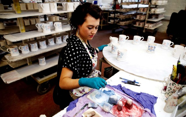 A worker prints a design onto a souvenir mug to commemorate the wedding of Britain's Prince Harry and Meghan Markle at the Emma Bridgewater Factory, in Hanley, Stoke-on-Trent, Briatin March 28, 2018. Picture taken March 28, 2018. REUTERS/Carl Recine