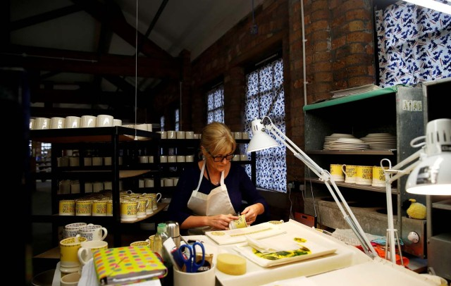 A worker adds transfers to mugs commemorating the wedding of Britain's Prince Harry and Meghan Markle at the Emma Bridgewater Factory, in Hanley, Stoke-on-Trent, Britain March 28, 2018. Picture taken March 28, 2018. REUTERS/Carl Recine