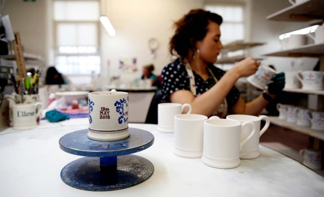 A worker prints a design onto a souvenir mug to commemorate the wedding of Britain's Prince Harry and Meghan Markle at the Emma Bridgewater Factory, in Hanley, Stoke-on-Trent, Britain March 28, 2018. Picture taken March 28, 2018. REUTERS/Carl Recine