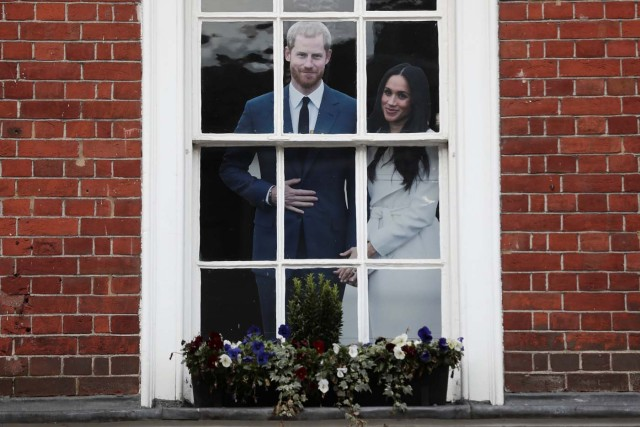 A life size cut out of Britain's Prince Harry and his fiancee Meghan Markle, stands in the window of a souvenir shop near Windsor Castle in Windsor, Britain, April 1, 2018. Picture taken April 1, 2018. REUTERS/Simon Dawson