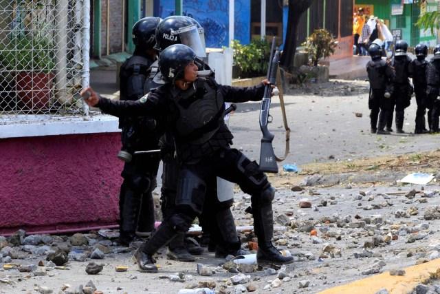 Un policía antidisturbios arroja una piedra contra los estudiantes universitarios durante una protesta contra las reformas que implementan cambios en los planes de pensiones del Instituto Nicaragüense de Seguridad Social (INSS) en Managua, Nicaragua, abril 19,2018.REUTERS / Oswaldo Rivas