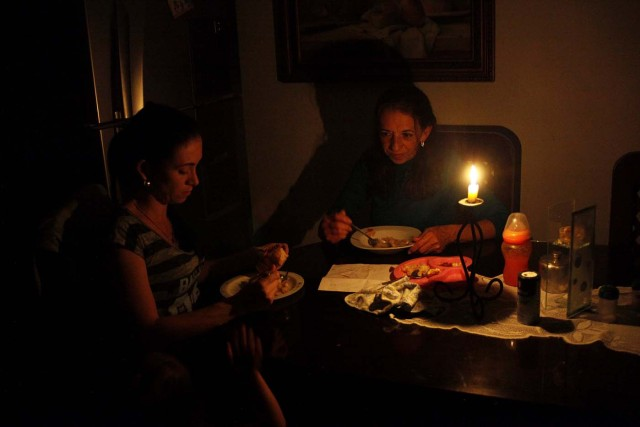 Carmenza Herrera (C) and her family use a candle to illuminate the table while they dine, during a blackout in San Cristobal, Venezuela, April 19, 2018. Picture taken April 19, 2018. REUTERS/Carlos Eduardo Ramirez