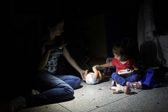 Monica Lizcano uses light from a phone while she plays with her daughter Valentina, during a blackout in San Cristobal, Venezuela, April 19, 2018. Picture taken April 19, 2018. REUTERS/Carlos Eduardo Ramirez