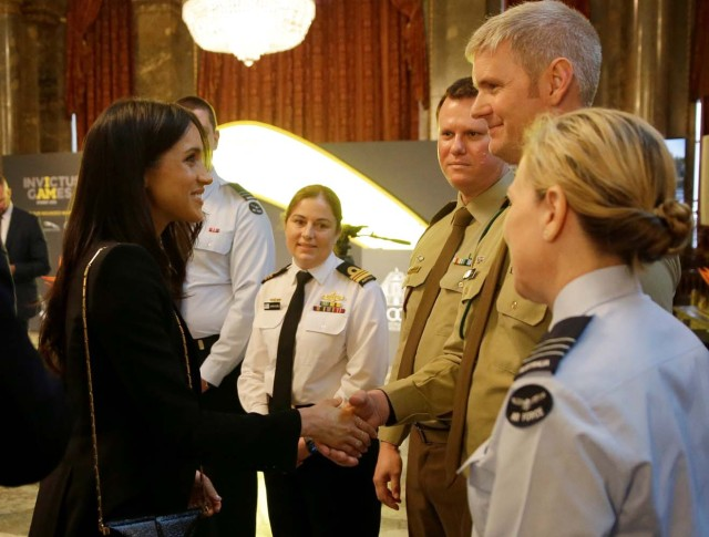 Britain's Prince Harry and Meghan Markle speak to members of the Australian Defence Force during a reception celebrating the forthcoming Invictus Games Sydney 2018, hosted by Malcolm Turnbull, Prime Minister of Australia, and his wife Lucy Turnbull, at Australia House in London, Britain April 21, 2018. Alastair Grant/Pool via Reuters