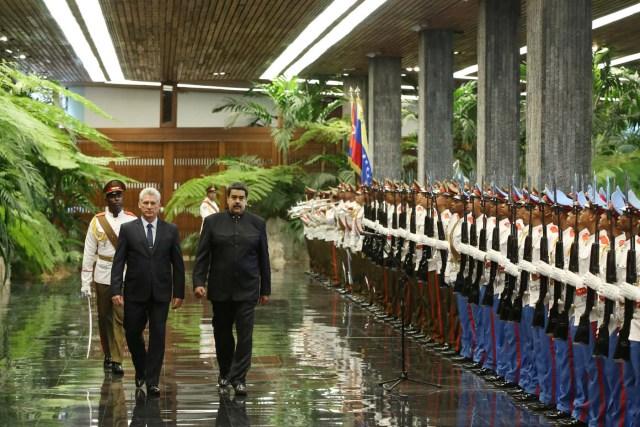 Cuban President Miguel Diaz-Canel (L) and Venezuela's President Nicolas Maduro review an honour guard during a ceremony at the Revolution Palace in Havana, Cuba April 21, 2018. REUTERS/Alexandre Meneghini