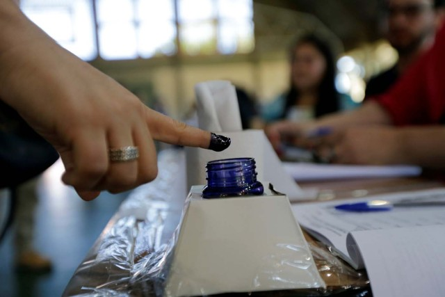 A woman inks his finger before casting her vote during elections in Asuncion, Paraguay, April 22, 2018. REUTERS/Mario Valdez