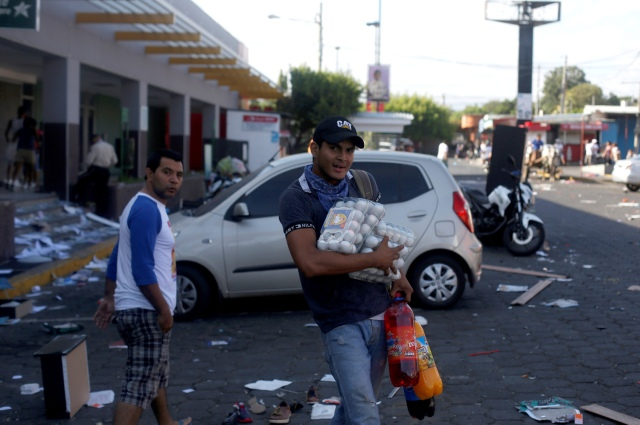 A man with goods looted from a store walks along a street after protests over a controversial reform to the pension plans of the Nicaraguan Social Security Institute (INSS) in Managua, Nicaragua April 22, 2018. REUTERS/Jorge Cabrera