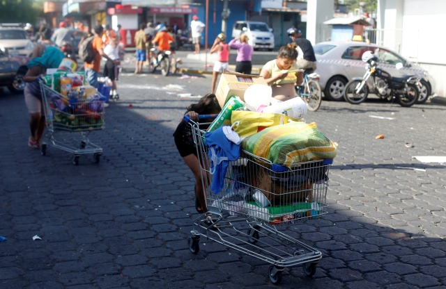 Gente se lleva mercadería saqueada de un supermercado en carritos por las calles después de protestas contra una controvertida reforma del sistema de pensiones en Managua, Nicaragua, abril 22, 2018. REUTERS/Jorge Cabrera - RC1EF7175E60