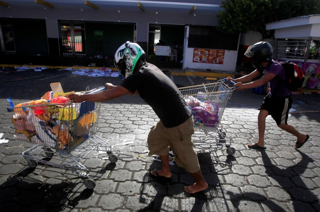 People with goods looted from a store walk pushing a shopping trolleys along a street after protests over a reform to the pension plans of the Nicaraguan Social Security Institute (INSS) in Managua, Nicaragua April 22, 2018. REUTERS/Jorge Cabrera