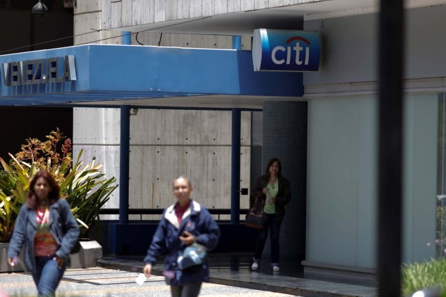 People walk outside a branch of Citi bank in Caracas, Venezuela April 6, 2018. REUTERS/Marco Bello