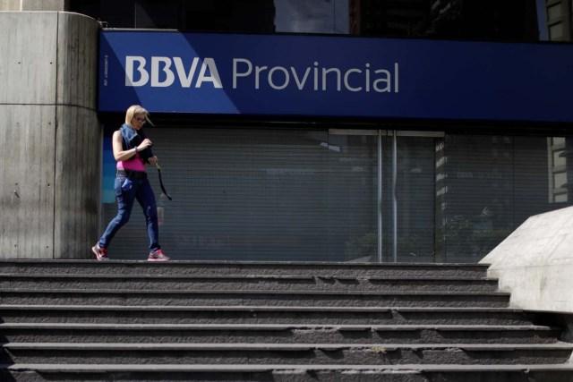 A woman walks outside a branch of BBVA Provincial bank in Caracas, Venezuela April 6, 2018. Picture taken April 6, 2018. REUTERS/Marco Bello