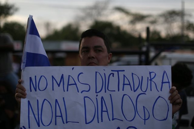 """A man holds a poster that reads """"no more dictatorship, no to dialog"""" during a memorial for journalist Angel Gahona in Managua, Nicaragua on April 25, 2018. REUTERS/Jose Cabezas"""