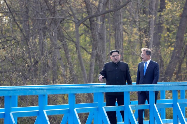 South Korean President Moon Jae-in and North Korean leader Kim Jong Un walk together on a bridge at the truce village of Panmunjom inside the demilitarized zone separating the two Koreas, South Korea, April 27, 2018. Korea Summit Press Pool/Pool via Reuters