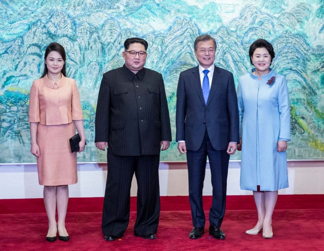 South Korean President Moon Jae-in and North Korean leader Kim Jong Un pose with Kim's wife Ri Sol Ju and Moon's wife Kim Jung-sook at the truce village of Panmunjom inside the demilitarized zone separating the two Koreas, South Korea, April 27, 2018. Korea Summit Press Pool/Pool via Reuters