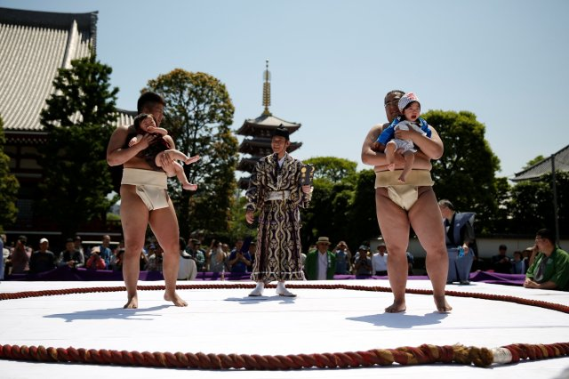 Babies cry as they are held up by amateur sumo wrestlers during a baby crying contest at Sensoji temple in Tokyo, Japan, April 28, 2018. In the contest two wrestlers each hold a baby while a referee makes faces and loud noises to make them cry. The baby who cries the loudest wins. The ritual is believed to aid the healthy growth of the children and ward off evil spirits. 160 children took part in the event in this year, the organiser said. REUTERS/Issei Kato