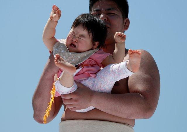 Un bebé llora en los brazos de un peleador de zumo amateur |FOTO: REUTERS/Issei Kato