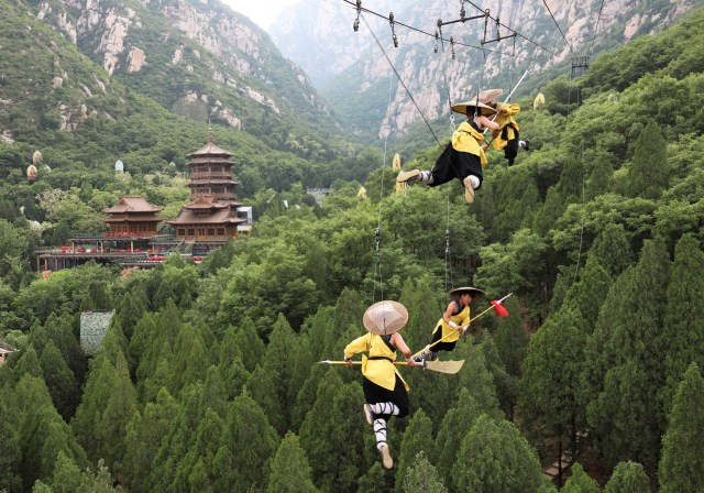 Shaolin martial arts students perform Kung Fu suspended on wires in a rehearsal for a live-action night show in Zhengzhou, Henan province, China April 28, 2018. Picture taken April 28, 2018. REUTERS/Stringer ATTENTION EDITORS - THIS IMAGE WAS PROVIDED BY A THIRD PARTY. CHINA OUT. NO COMMERCIAL OR EDITORIAL SALES IN CHINA.     TPX IMAGES OF THE DAY