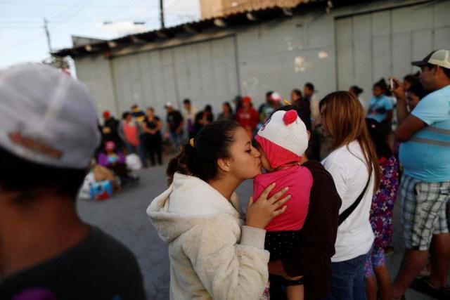 Una integrante de la caravana de inmigrantes provenientes de Centroamérica besa a un bebé mientras rezan antes de presentar un pedido de asilo en Estados Unidos, en Tijuana, México, 28 de abril de 2018. REUTERS/Edgard Garrido