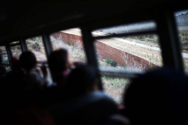 Members of a caravan of migrants from Central America ride on a bus past the border fence between Mexico and the U.S., to gather in a park prior to preparations for an asylum request in the U.S., in Tijuana, Mexico April 29, 2018. REUTERS/Edgard Garrido
