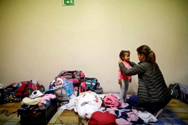 A woman dresses a girl while staying at a shelter with fellow members of a caravan of migrants from Central America, prior to preparations for an asylum request in the U.S., in Tijuana, Mexico April 29, 2018. REUTERS/Edgard Garrido