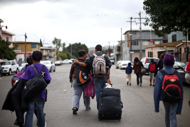 Members of a caravan of migrants from Central America carry their luggage before a gathering in a park prior to preparations for an asylum request in the U.S., in Tijuana, Mexico April 29, 2018. REUTERS/Edgard Garrido