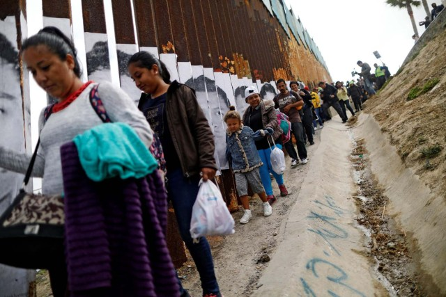 Members of a caravan of migrants from Central America walk next to the border fence between Mexico and the U.S., before a gathering in a park and prior to preparations for an asylum request in the U.S., in Tijuana, Mexico April 29, 2018. REUTERS/Edgard Garrido