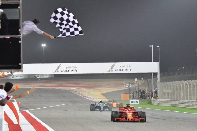 POOL01. Manama (Bahrain), 08/04/2018.- German Formula One driver Sebastian Vettel of Scuderia Ferrari (R) crosses finish line to win the 2018 Formula One Grand Prix of Bahrain at the Sakhir circuit near Manama, Bahrain, 08 April 2018. (Bahrein, Fórmula Uno) EFE/EPA/GIUSEPPE CACACE / POOL