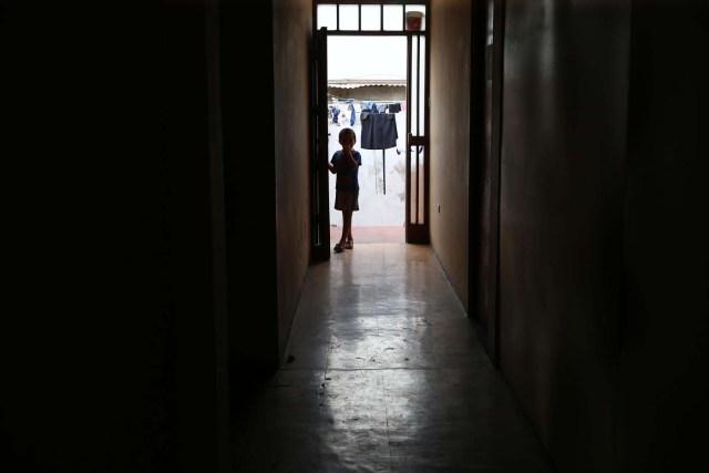 IMAGEN REFERENCIAL: Acompaña crónica PERÚ VENEZUELA - PER12 - LIMA (PERÚ) , 26/4/2018.- Fotografía tomada el 25 de abril de 2018, de un niño, hijo de inmigrantes que se asoma a la puerta de la vivienda donde temporalmente residen en uno de los distritos mas populosos de la capital, San Juan de Lurigancho, en Lima (Perú). La solidaridad y caridad imperan en el improvisado albergue que un pequeño empresario peruano ha instalado para dar un primer techo a los venezolanos recién llegados a Lima, desde donde intentan comenzar una nueva vida a la que se vieron abocados por la crudeza de la crisis que atraviesa Venezuela. EFE / Ernesto Arias