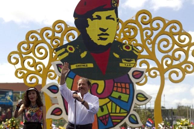 MAN01. MANAGUA (NICARAGUA), 05/03/14.- El presidente de Nicaragua, Daniel Ortega, junto a su esposa, la primera dama Rosario Murillo, saludan a simpatizantes sandinistas durante un acto político en el marco de la conmemoración del primer aniversario de la muerte del presidente venezolano Hugo Chávez en el Paseo de Bolívar a Chávez en Managua (Nicaragua) hoy, miércoles 5 de marzo de 2014. EFE/Jorge Torres.