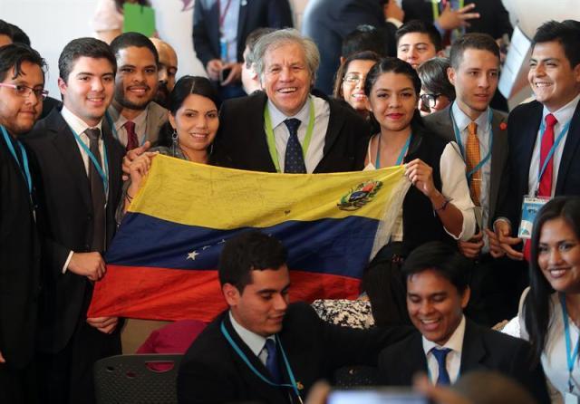 El secretario general de la Organización de Estados Americanos (OEA), Luis Almagro (c), posa para una foto con un grupo de jóvenes que sostienen una bandera venezolana hoy, miércoles 11 de abril de 2018, durante el Foro de los Jóvenes, una de las reuniones preparatorias para la Cumbre de las Américas, en Lima (Perú). EFE