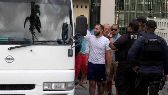 Es hora de irse: los policías guían a los detenidos venezolanos a un autobús después de que fueron procesados en la Embajada de Venezuela en Puerto España el viernes. Foto de Roger Jacob en Newsday