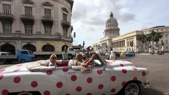 Turistas se pasean en un auto clásico cerca del Capitolio, en La Habana. (Archivo)