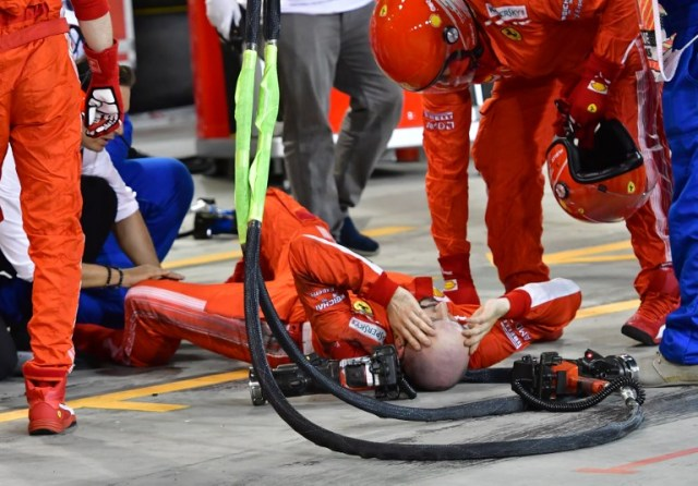 A pitman receives medical assistant following an accident during the pit stop of Ferrari's Finnish driver Kimi Raikkonen during the Bahrain Formula One Grand Prix at the Sakhir circuit in Manama on April 8, 2018.  / AFP PHOTO / POOL AND AFP PHOTO / Giuseppe CACACE