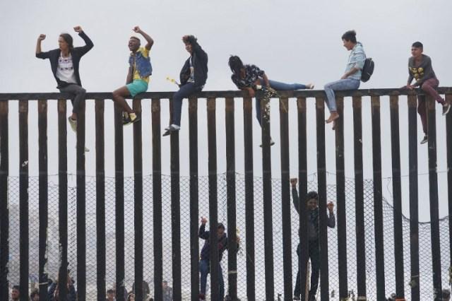 Manifestantes de caravanas migrantes suben la valla fronteriza entre Estados Unidos y México durante un mitin, el 29 de abril de 2018, en San Ysidro, California. Estados Unidos ha amenazado con arrestar a unos 100 migrantes centroamericanos si intentan colarse desde la frontera entre Estados Unidos y México donde se han reunido, lo que provocó que el presidente estadounidense Donald Trump ordene refuerzos de tropas en la frontera.  Sandy Huffaker / AFP