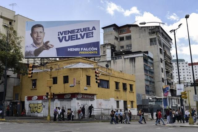 Vista de una cartelera con publicidad electoral del candidato presidencial opositor venezolano Henri Falcon en Caracas el 11 de mayo de 2018. Los ciudadanos venezolanos enfrentarán elecciones presidenciales el 20 de mayo en medio de una severa crisis socioeconómica, con hiperinflación, estimada en 13.800% por el FMI para 2018 - y la escasez de alimentos, medicinas y otros productos básicos. / AFP PHOTO / Luis ROBAYO