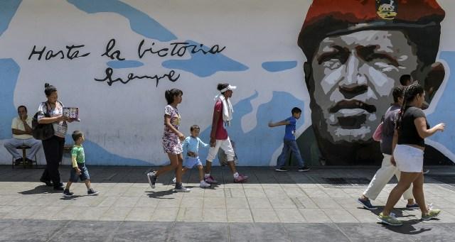 La gente camina por un graffiti con una imagen del difunto presidente Hugo Chávez en Caracas el 11 de mayo de 2018. Los ciudadanos venezolanos enfrentarán elecciones presidenciales el 20 de mayo en medio de una severa crisis socioeconómica, con hiperinflación, estimada en 13.800% por el FMI para 2018 - y escasez de alimentos, medicinas y otros productos básicos. / AFP PHOTO / Luis ROBAYO