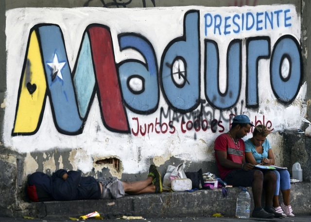 Personas junto a un graffiti alusivo a la publicidad electoral del presidente venezolano y candidato a la reelección, Nicolás Maduro Caracas, el 11 de mayo de 2018. Los ciudadanos venezolanos se enfrentarán a las elecciones presidenciales del 20 de mayo en medio de una crisis socioeconómica severa, con hiperinflación estimada en 13.800% por el FMI para 2018, y la escasez de alimentos, medicinas y otros productos básicos. / AFP PHOTO / Luis ROBAYO