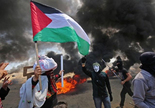 Un palestino sosteniendo su bandera nacional camina en el humo de neumáticos quemados junto a un manifestante con una máscara anónima durante enfrentamientos con las fuerzas israelíes en la frontera con la franja de Gaza al este de Khan Yunis el 14 de mayo de 2018, mientras los palestinos protestan por la inauguración de la embajada de los Estados Unidos después de su controvertido traslado a Jerusalén. / AFP PHOTO / SAID KHATIB