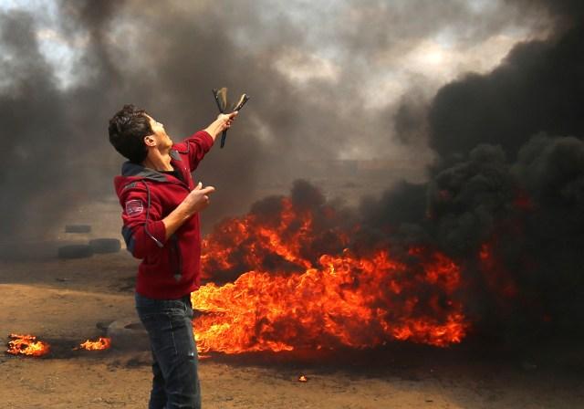 Un palestino usa un tirachinas durante los enfrentamientos con las fuerzas israelíes a lo largo de la frontera con la franja de Gaza al este de Khan Yunis el 14 de mayo de 2018, mientras los palestinos protestan por la inauguración de la embajada de Estados Unidos tras su controvertido traslado a Jerusalén. / AFP PHOTO / SAID KHATIB