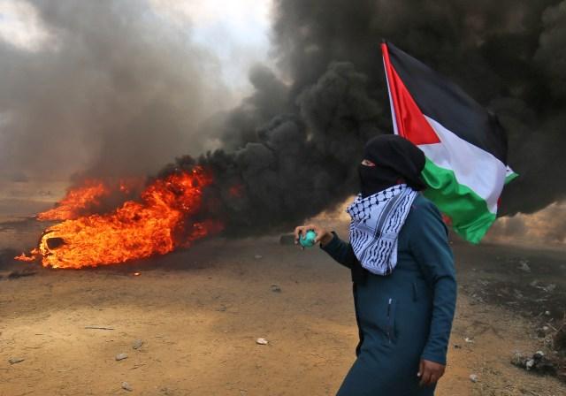Un palestino sosteniendo su bandera nacional camina en el humo de las llantas incendiadas durante los enfrentamientos con las fuerzas israelíes a lo largo de la frontera con la franja de Gaza al este de Khan Yunis el 14 de mayo de 2018, mientras los palestinos protestan por la inauguración de la embajada muévete a Jerusalén / AFP PHOTO / SAID KHATIB